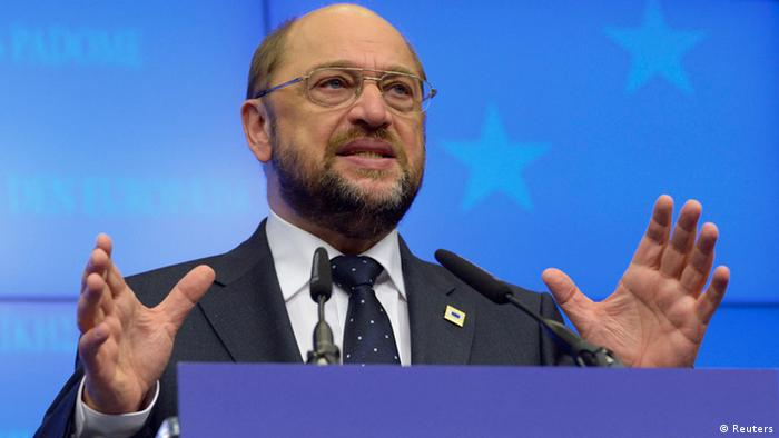 A balding man with a beard and eyeglasses opens his raised palms as he explains something to an off-camera crowd from a podium. (Photo: REUTERS/Eric Vidal)