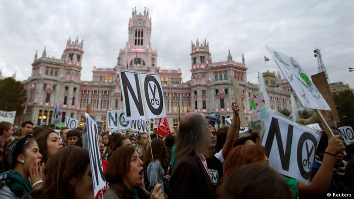 Protesters hold placards during a demonstration in front of Madrid's City Hall