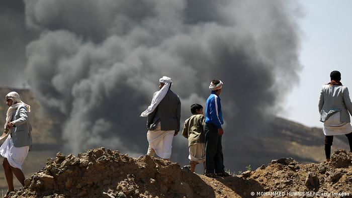 Yemeni watch as smoke billows following an accidental explosion at an army ammunition depot in the Yemeni capital of Sanaa on October 18, 2012. According to a military source, a rocket fired during an army training session hit the warehouse by mistake. AFP PHOTO/MOHAMMAD HUWAIS (Photo credit should read MOHAMMED HUWAIS/AFP/Getty Images)