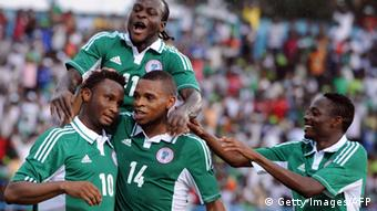 Nigerian striker Victor Moses jumps on goal scorer Mikel Obi (L), Umar Zango (C) and Amed Musa celebrating a Nigerian fourth goal against Liberia during the 2013 African Cup of Nations second leg qualifying match between the two countries at Calabar October 13, 2012. Nigeria defeated Liberia 6 - 1 to qualify for the tournament to be held in South Africa next year. AFP PHOTO/PIUS UTOMI EKPEI . (Photo credit should read PIUS UTOMI EKPEI/AFP/GettyImages)