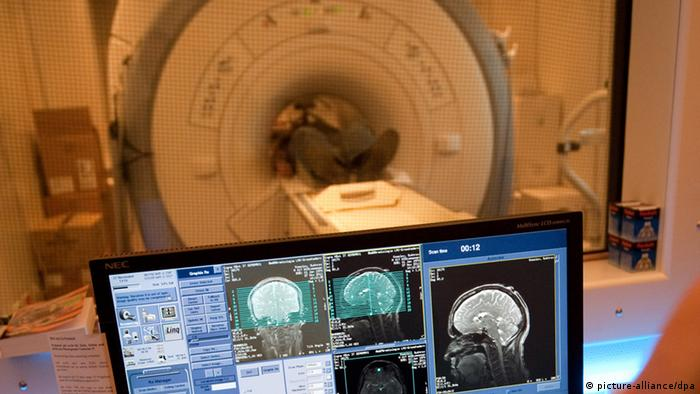 A screen with brain images is seen in front of an MRI machine