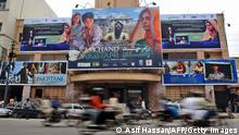 TO GO WITH STORY BY DANNY KEMP 'ENTERTAINMENT-PAKISTAN-INDIA-FILM-POLITICS' In this photograph taken on August 2, 2008 Pakistani commuters drive past a cinema displaying a billboard of the Indian and Pakistan joint venture movie 'Ramchand Pakistani' in Karachi. As tensions mount between India and Pakistan, the release in both countries of a Pakistani film about a young boy held in an Indian jail is being hailed as a welcome boost for cultural ties. The movie, 'Ramchand Pakistani', which opened in Pakistan on August 1 and in India on August 22, could also help revive Pakistan's flagging film industry after years in the shadow of India's hugely successful Bollywood. AFP PHOTO/ Asif HASSAN (Photo credit should read ASIF HASSAN/AFP/Getty Images)