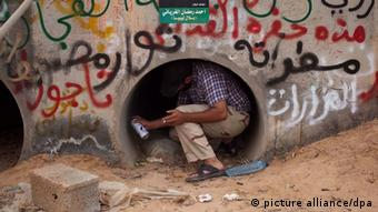 epa02975684 A Libyan rebel fighter paints on the wall of one of the pipes where Muammar Gaddafi allegedly found hiding, in Sirte, Libya, 21 October 2011. Libyan deposed leader Muammar Gaddafi was arrested on 20 October, some witnesses said he was found hiding in a drainage pipe in Sirte. He died later, along with his son Motassim. EPA/GUILLEM VALLE +++(c) dpa - Bildfunk+++