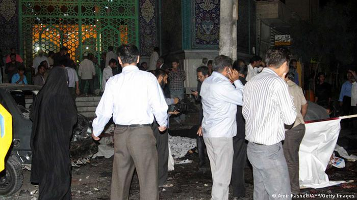 People survey the carnage outside Jameh mosque in the southeastern Iranian city of Zahedan on July 15, 2010. Two suicide bombings at a Shiite mosque in heavily Sunni southeast Iran killed more than 20 people, including worshippers and members of the Revolutionary Guards, state media reported. The attack came as people celebrated the birthday of Imam Hussein, grandson of the Muslim Prophet Mohammed, a day also set apart each year to honour the Revolutionary Guards. More than 100 people were wounded in the attacks, which came only minutes apart, at the Jamia mosque in the restive city of Zahedan, capital of southeastern Sistan-Baluchestan province bordering Afghanistan and Pakistan. AFP PHOTO / IRNA / AMIR RASHEKI (Photo credit should read AMIR RASHEKI/AFP/Getty Images)