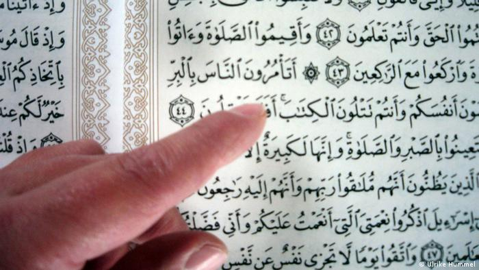 A finger pointing at words in the Koran Photo: Ulrike Hummel