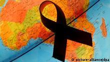 ILLUSTRATION - Eine rote Aids-Schleife liegt auf einem Globus über dem Kontinent Afrika, aufgenommen in Frankfurt (Oder) am 29.11.2010. Die WHO hat den 1. Dezember als den Weltaidstag 1988 ausgerufen. Rund um den Globus erinnern am 1. Dezember verschiedenste Organisationen an das Thema Aids und rufen dazu auf, aktiv zu werden und Solidarität mit HIV-Infizierten, Aids-Kranken und den ihnen nahestehenden Menschen zu zeigen. Foto: Patrick Pleul dpa/lbn