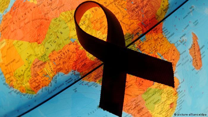 Eine rote Aids-Schleife liegt auf einem Globus über dem Kontinent Afrika (Foto: Patrick Pleul dpa/lbn)
