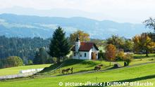 Eine Kapelle in bergigem Land, davor zwei Menschen, die Pferde führen.