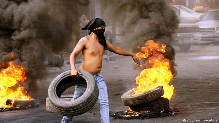 A supporter of the Lebanese Future party sets up a road block with burning tyres in the southern city of Sidon, Lebanon, 20 October 2012.
