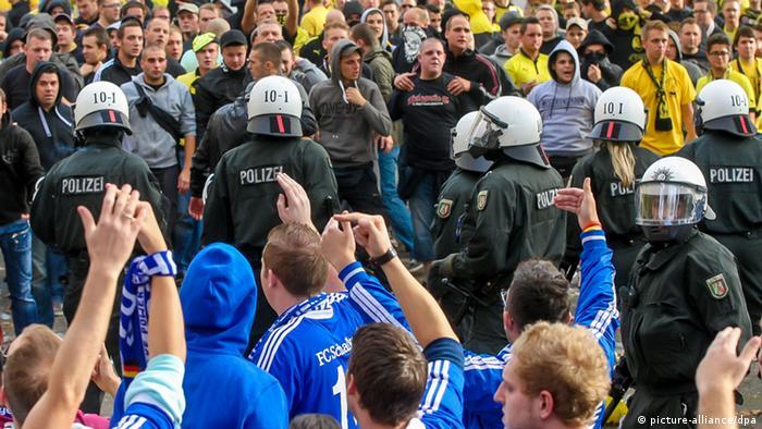 Anhänger von Borussia Dortmund und dem FC Schalke 04 stehen sich gegenüber, getrennt von der Polizeit (Foto: Stephan Schütze/dpa)