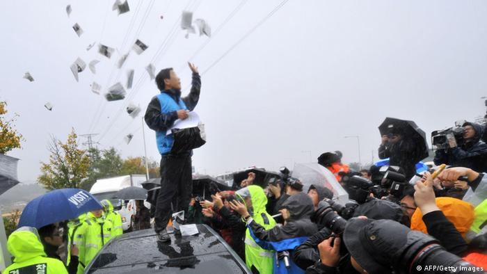 GettyImages 154540290 Park Sang-Hak (C), an activist and former defector from North Korea, scatters anti-Pyongyang leaflets as police block his planned rally near the tense border on a roadway in Paju, north of Seoul, on October 22, 2012. South Korean troops and riot police prevented activists from launching anti-Pyongyang leaflets across the border, after North Korea threatened a 'merciless' military response. AFP PHOTO / JUNG YEON-JE (Photo credit should read JUNG YEON-JE/AFP/Getty Images)