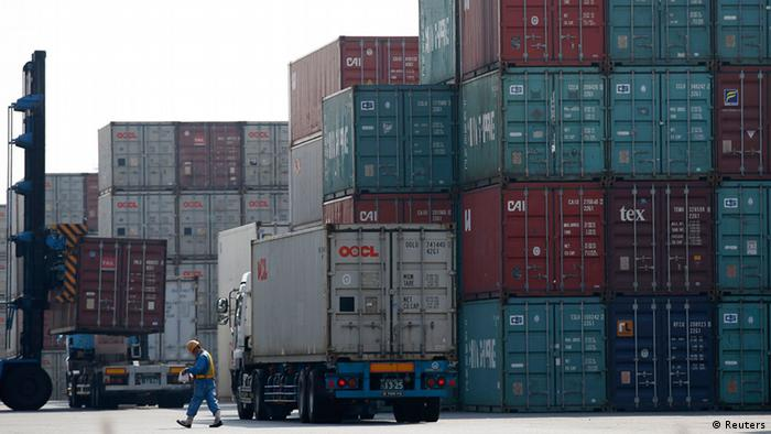 A worker walks in a shipping container area at a port in Tokyo October 22, 2012.