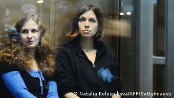 Alyokhina and Tolokonnikova sitting in a glass-walled cage in a court in Moscow (Photo: Natalia Kolesnikova)