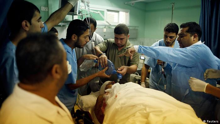 Palestinian medics treat a man wounded in an Israeli air strike, at a hospital in the northern Gaza Strip October 22, 2012. Israeli forces killed two Palestinian militants during an incursion in the northern Gaza Strip on Monday that touched off clashes with gunmen from the governing Hamas movement, local officials said. Israel's military said the air force struck a Palestinian rocket crew after a routine (army) patrol in the area came under mortar attack. REUTERS/Mohammed Salem (GAZA - Tags: POLITICS CIVIL UNREST)