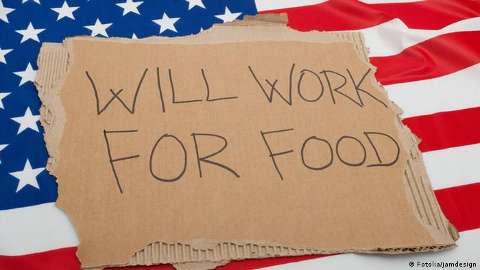 A sign that reads 'will work for food' on top of a flag of the US