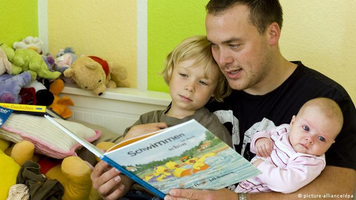 Andreas Lange mit seinem sohn Janne (4) und seiner drei Monate alten Tocher Fiona beim Vorlesen aus einem Bilderbuch , aufgenommen am 17.07.2008 in Frankfurt (Oder). Der 34-Jährige Vater hat drei Monate Elternzeit genommen. Foto: Patrick Pleul +++(c) dpa - Report+++
