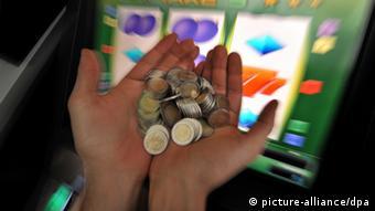 Ein Spieler hält vor einem Glücksspielautomaten Geld in seinen Händen