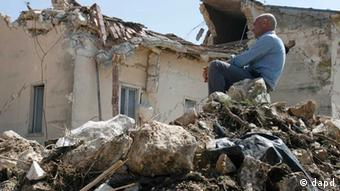 A man sits on rubble in the village of Onna, a day after a powerful earthquake struck the Abruzzo region in central Italy (c) Alessandra Tarantino, File/AP/dapd