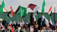 Palestinian women hold Qatari and their national flags, alongside pictures of the Emir of Qatar Sheik Hamad bin Khalifa al-Thani as they wait for his arrival in Gaza City on October 23, 2012. Qatar's emir was warmly welcomed on a landmark tour of the Gaza Strip in the first such visit by a head of state since the Islamist Hamas movement took over in 2007. AFP PHOTO/MAHMUD HAMS (Photo credit should read MAHMUD HAMS/AFP/Getty Images)