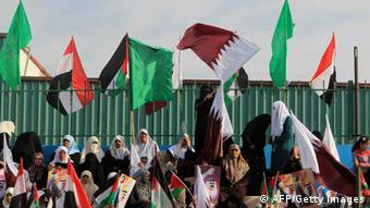 Palestinian women hold Qatari and their national flags (photo: MAHMUD HAMS/AFP/Getty Images)