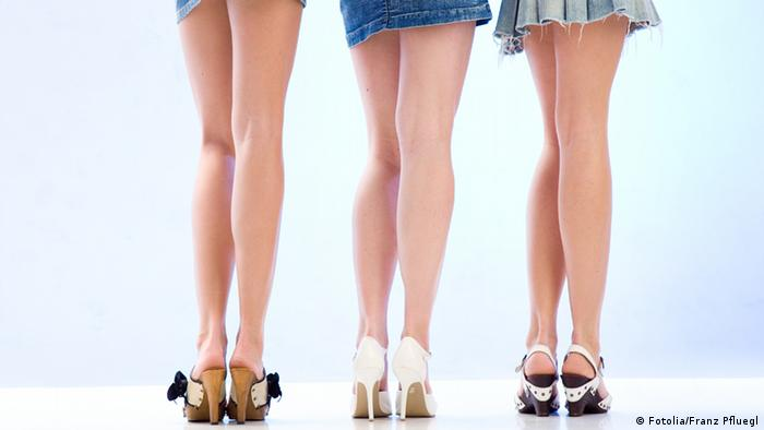 The legs of three women wearing short skirts