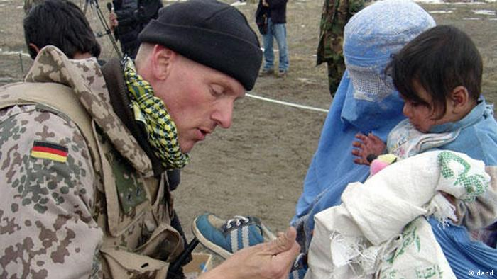 German soldier helps Afghan mother and child as part of ISAF contingent in Kabul, Afghanistan. Photo: AP Photo/ HO