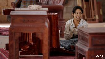 Asiatin sitzt neben Rosenholz-Tisch (Foto:Eugene Hoshiko/AP/dapd)
