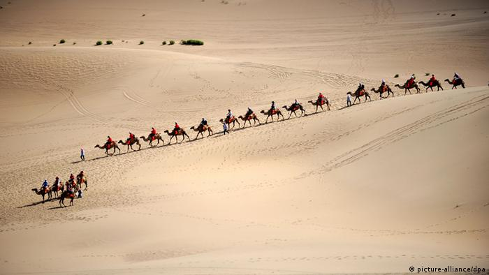 Tourists ride camels in a line on the Singing-Sand Dunes in Dunhuang city, northeast Chinas Gansu province.