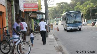 A bus pulls up on a bus street while Brazilians walk on the sidewalk. (Photo: DW/Sam Cowie)