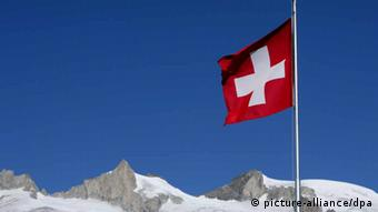 ARCHIV - Die Schweizer Landesfahne weht am Großen Aletschgletscher unweit der Riederalp im Wind (Archivfoto vom 16.10.2007). Nach schwierigen Verhandlungen wollen Deutschland und die Schweiz heute (Donnerstag) ein Zusatzprotokoll zu ihrem umstrittenen Steuerabkommen unterzeichnen. Darin verpflichtet sich die Schweiz nach Angaben von Diplomaten zur Zahlung höherer Abgeltungszahlungen auf Schwarzgeld-Guthaben von Deutschen, als dies bisher vorgesehen war. Konkrete Zahlen sollen aber erst nach der Unterschriftsleistung in Bern bekanntgegeben werden. Foto: Patrick Pleul dpa (zu dpa 0024 am 05.04.2012) +++(c) dpa - Bildfunk+++
