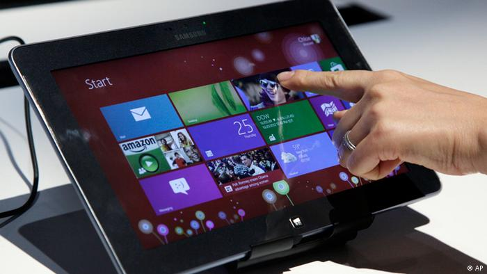 A person tries a Samsung tablet computer running Windows 8 at the launch of Microsoft Windows 8, in New York, Thursday, Oct. 25, 2012. Windows 8 is the most dramatic overhaul of the personal computer market's dominant operating system in 17 years. (Foto:Richard Drew/AP/dapd).