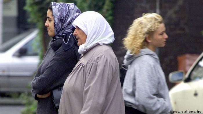 Two Turkish women with headscarves pass a blond woman as they go shopping Photo: Roland Weihrauch dpa/lsw