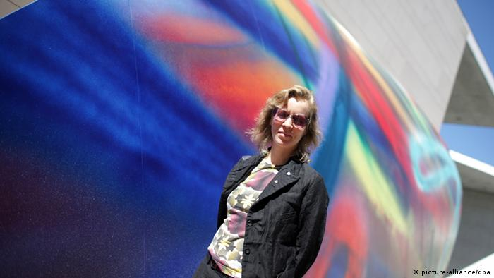 Художница Катарина Гроссе на фоне одного из своих произведений