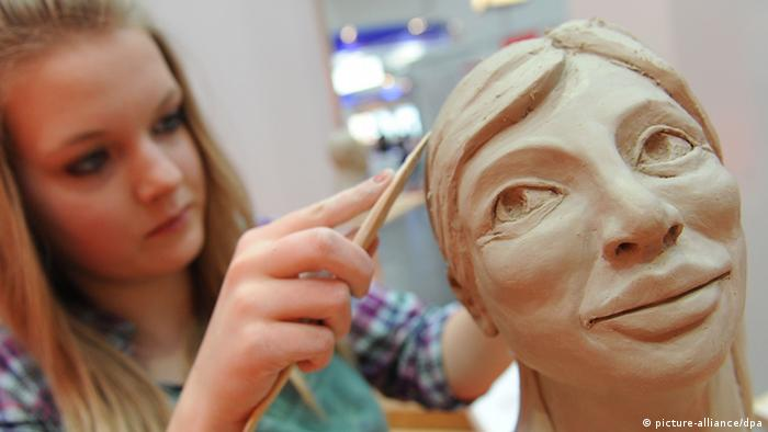 A teenage girl shapes a clay figure (Photo: Peter Steffen)