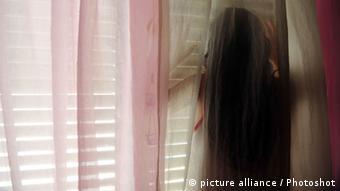 Ein Mädchen hinter einer Schattenwand (Foto: picture alliance/Photoshot)