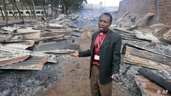 Bishop Sospeter Njenga surveys a row of houses belonging to Kikuyus, which were burned to the ground during ethnic clashes. (Photo: AP Photo/Ben Curtis)