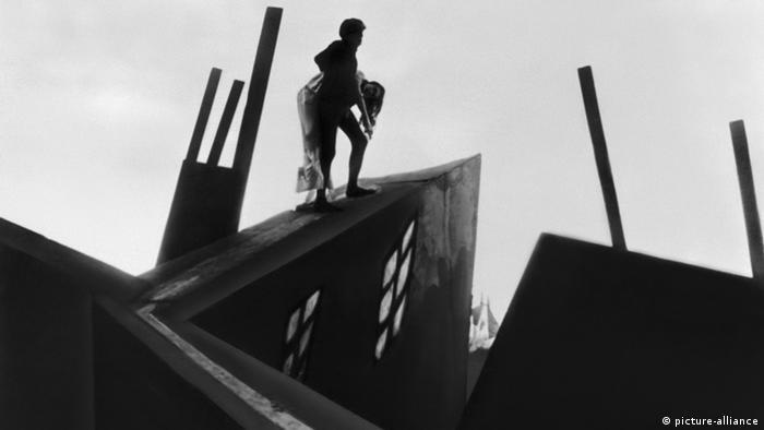 Foto em preto e branco com duas pessoas caminhando em telhado inclinado