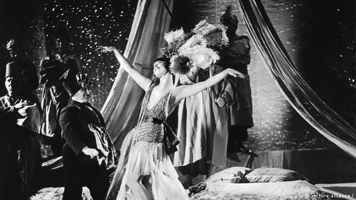 Foto em preto e branco mostra cena dos anos 1920 com mulher de plumas na cabeça dançando e observada por homem