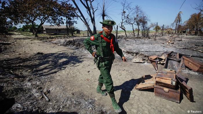 A soldier walks amid the rubble of a neighborhood in Pauktaw township that was burned in recent violence (Photo: REUTERS/Soe Zeya Tun)
