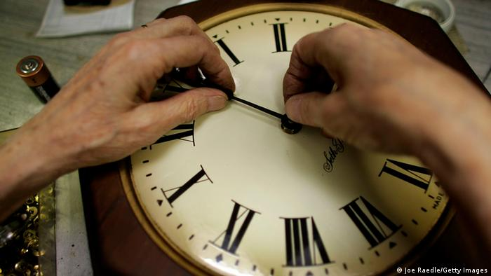 Hands fixing an old-fashioned clock Photo by Joe Raedle/Getty Images)
