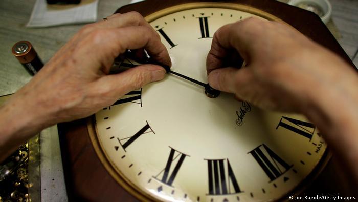 Zwei Hände drehen an den Zeigern einer Uhr. Foto: dpa
