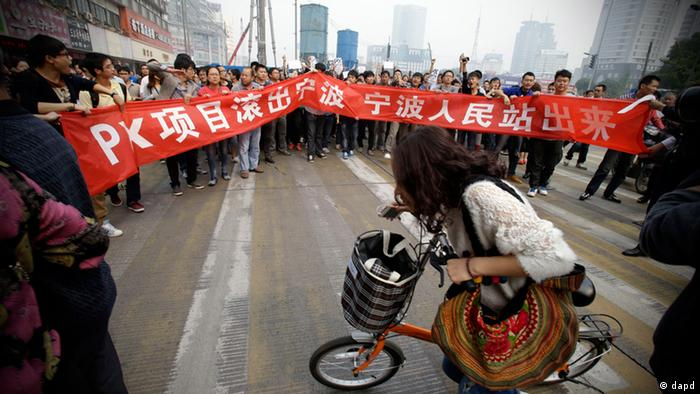 Protesters march with a banner which reads Project PX get out of Ningbo, Ningbo people stand up in Zhejiang province's Ningbo city, protesting the proposed expansion of a petrochemical factory Sunday, Oct. 28, 2012. Thousands of people in the eastern Chinese city clashed with police Saturday while protesting the proposed expansion of the factory that they say would spew pollution and damage public health, townspeople said. (AP Photo/Ng Han Guan)