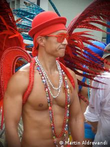 A man wears feathers and beads on a bare chest at Taipei's gay pride parade; Photo: DW/Martin Aldrovandi