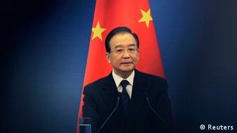 China's Premier Wen Jiabao stands in front of a Chinese national flag as he attends a joint news conference of the fifth trilateral summit among China, South Korea and Japan at the Great Hall of the People in Beijing, in this May 13, 2012 file photo. The family of Chinese Premier Wen Jiabao, a leader known for his humble roots and compassion for ordinary Chinese, has accumulated massive wealth during his time in power, the New York Times reported on October 26, 2012. REUTERS/Petar Kujundzic/Files (CHINA - Tags: POLITICS BUSINESS)