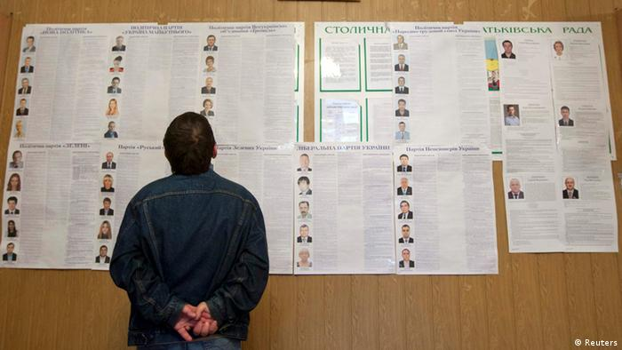 A man looks at an information board about the candidates at a polling station during the parliamentary elections. (Photo:REUTERS/Valentyn Ogirenko)