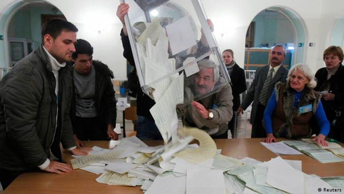 Members of a local electoral commission empty a ballot box at a polling station after voting day in Kiev October 28, 2012. (c) REUTERS/Gleb Garanich