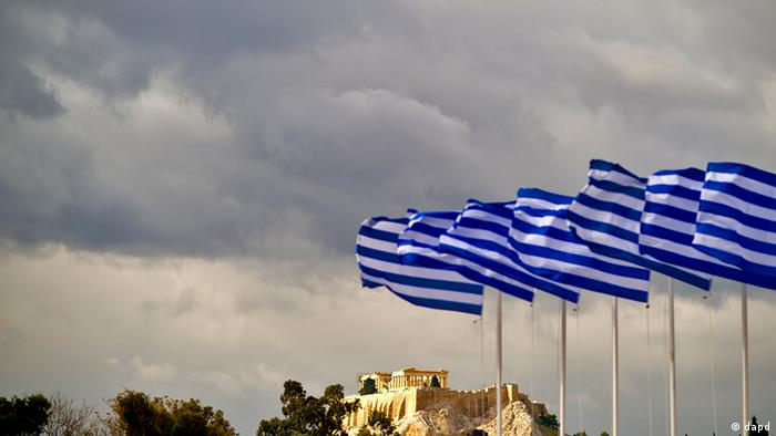 A photo of cloudy skies with Greek flags blowing in the breeze in from the of the Acropolis (from 13.11.11). (Photo via Axel Schmidt/dapd)