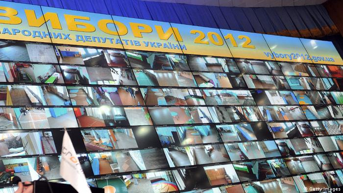 Multi-screen wall of data surveillance cameras at different polling stations