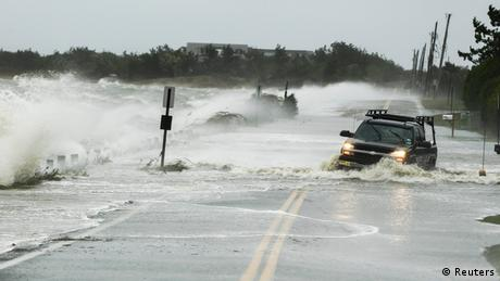 A truck drives through water pushed over a road by hurricane Sandy in Southampton, New York