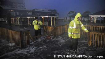 People walk through water on the beach near the time of high tide as Hurricane Sandy approaches October 29, 2012 in Atlantic City, New Jersey. Hurricane Sandy drove a deadly tidal surge into coastal cities along the eastern US coast and pushed storm-force winds, torrential rain and heavy snow deep inland. AFP PHOTO/Stan HONDA (Photo credit should read STAN HONDA/AFP/Getty Images)